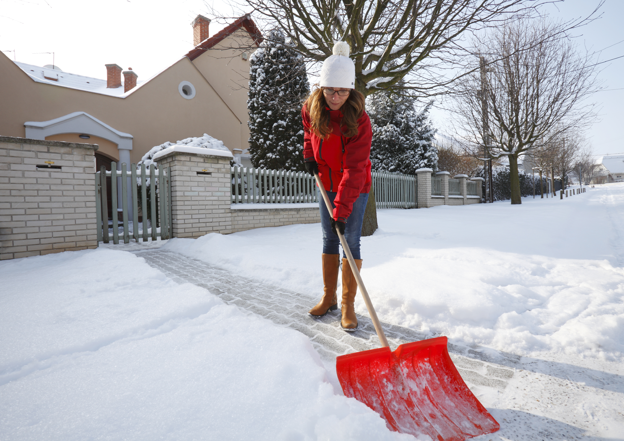 Woman shoveling and removing snow in front of her house in the suburb